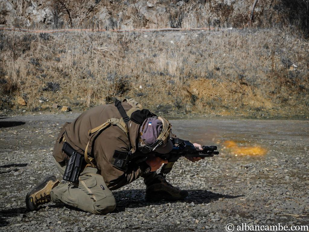 Instructor Zero réalise un tir accroupi avec flamme de bouche de canon.
